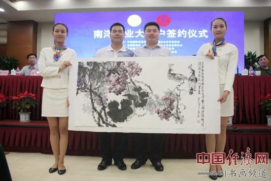 著名国画家李泽存(左)赠送国画表示祝贺,贵州茅台镇南洋酒业有限公司总经理蔡峰(右)代为接收。